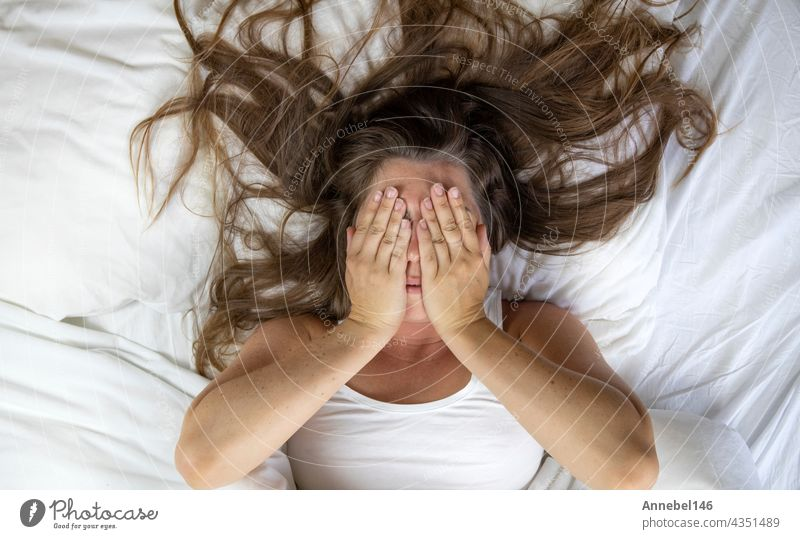 Young woman lying in bed suffering, tired woman covering face with hands, can't sleep feels exhaustand on white sheets in bedroom head ache bedroom closeup