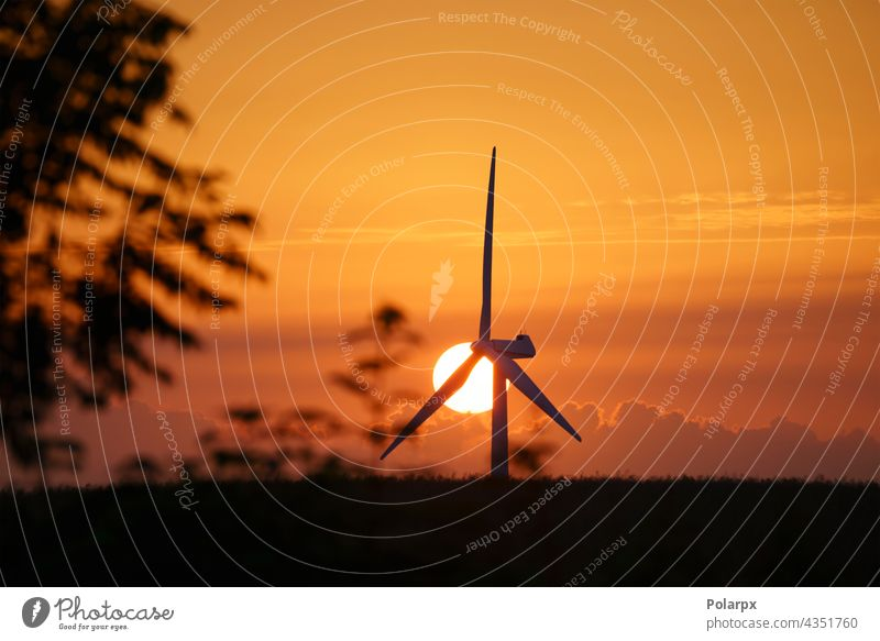 Windmill in a sunset in a rural summer landscape station farm efficiency field rotors green propeller blue mountain park natural clean wind turbines sunlight