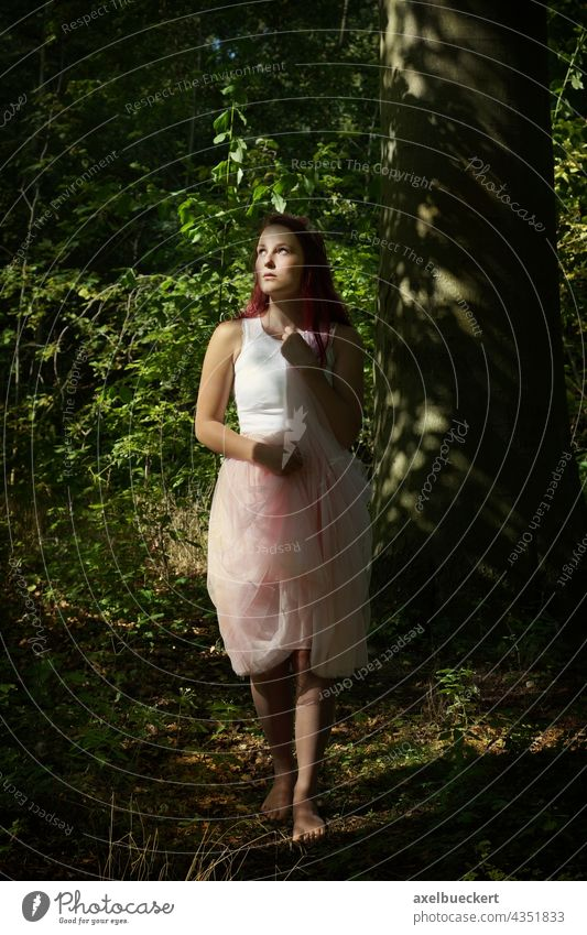young woman standing barefoot in tulle skirt in forest Young woman Fairy Elf wood nymph Forest Stand Barefoot Skirt Sunlight Mystic Nature Day Upward enchanted