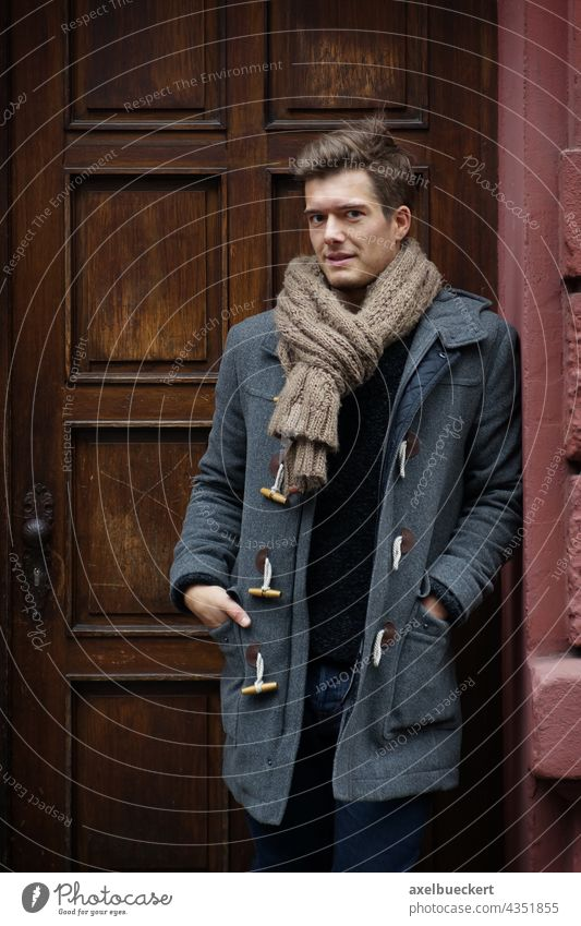 young man with duffle coat waits in the house entrance Young man Wait front door Entrance Winter Coat winter jacket Scarf Blonde Stand Lean