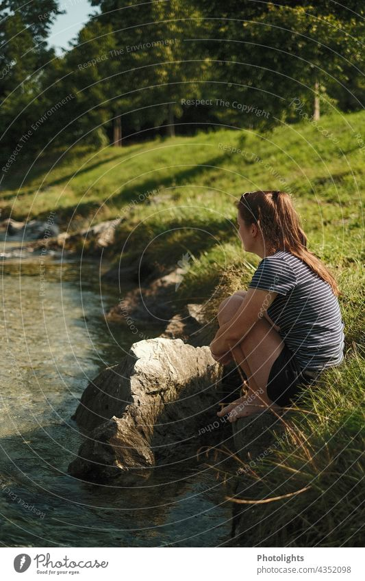Young woman sits on the bank of a small river and looks into the distance Contrast Shadow Exterior shot Colour photo Trust Happy Sit To enjoy Brook Relaxation