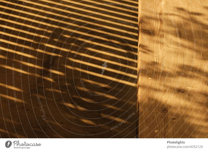 Shadow of a grid in front of wooden bench Grating Wooden board Wooden bench Warmth Light Sun Sunlight Rich in contrast Contrast Shadow play Colour photo