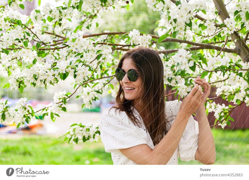 Attractive and beautiful young woman in sunglasses. Young woman caucasian ethnicity. Smiling and happy female is posing in white clothes. Cheerful pretty woman on blooming apple tree background.