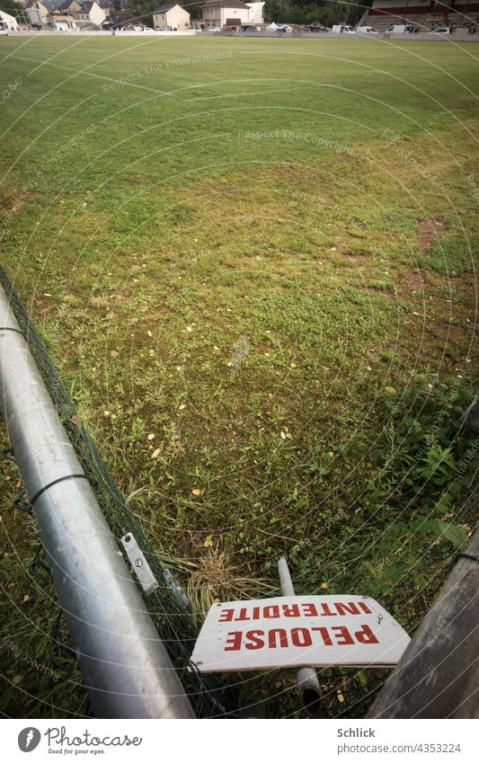 Sign with red inscription PELOUSE INTERDITE Do not enter lawn stands in the corner of a football field Foot ball Football pitch sign Lawn No trespassing French