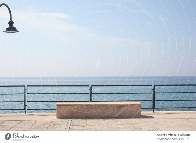 Stone bench on a seaside pier on Italian coast in morning light horizontal outdoor color image colorful nobody no people sky blue background front ocean nature