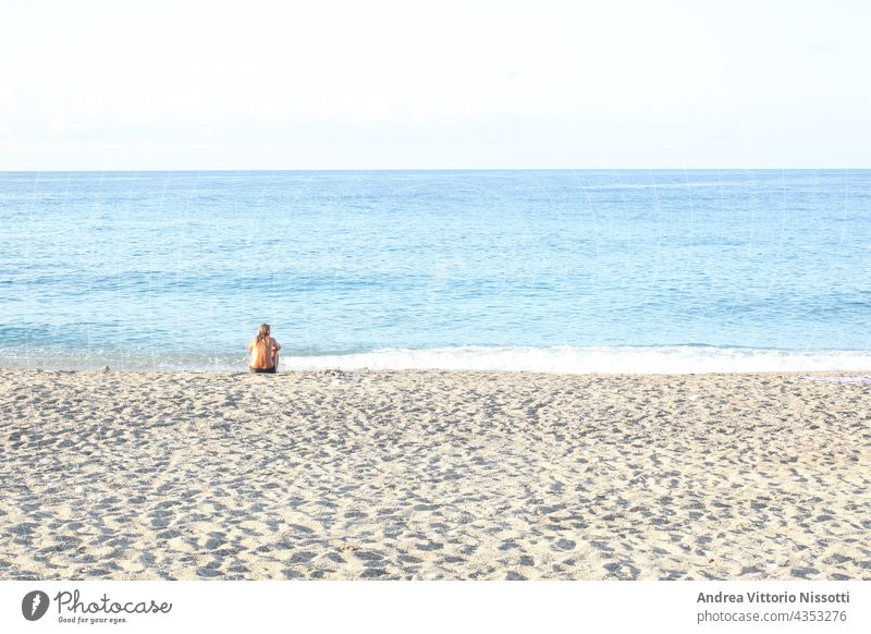 Woman sitting alone on a beach contemplating the sea with copy space for your text horizontal color image people caucasian outdoor seaside summer holiday