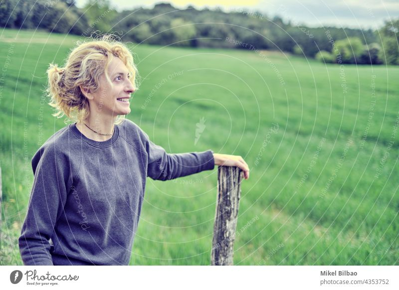 Portrait of a young mature caucasian woman standing outdoor leaning on a path pole in spring time. lifestyles people women blond blonde only portrait adult