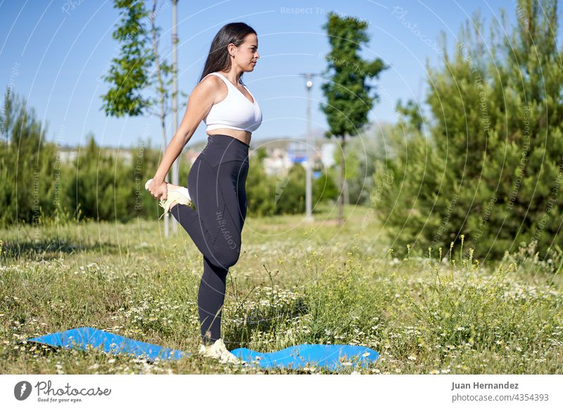 young woman doing gymnastic exercises on the grass. Female model in sportswear pretty female outside fitness training stretching athlete exercising wellness