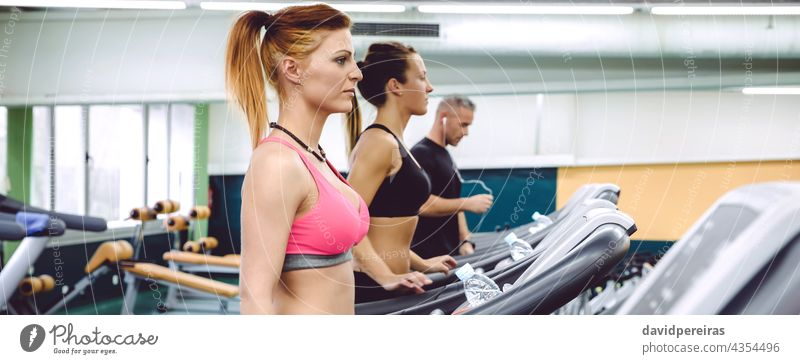 People training over treadmills on fitness center panorama people group woman machine copy space jogging warming up cardio running class sport banner exercise