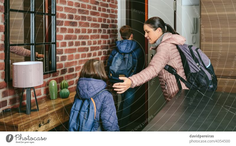 Family with emergency backpacks leaving their front door quickly family leaving home evacuation go out bug out bag hurry house people disaster safety female
