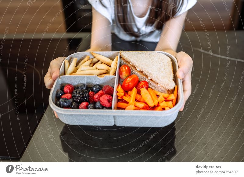Unrecognizable girl showing lunch box filled with healthy food unrecognizable vegetarian healthy snack veganism take-away lunch box compartments school