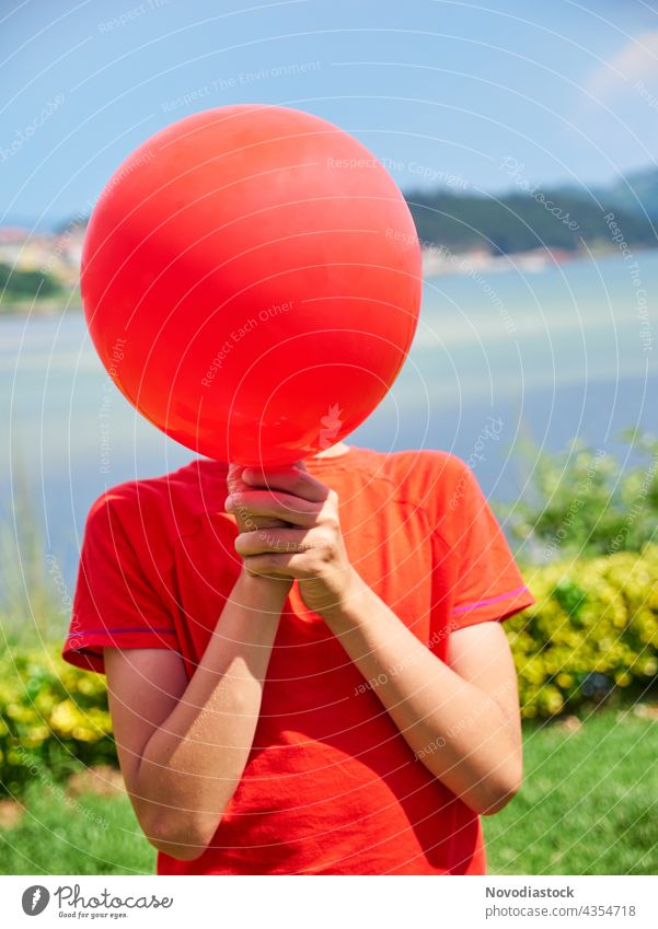 boy hiding face behind a red balloon alone background birthday casual casual clothes caucasian celebrate celebration child childhood colorful cover decorating