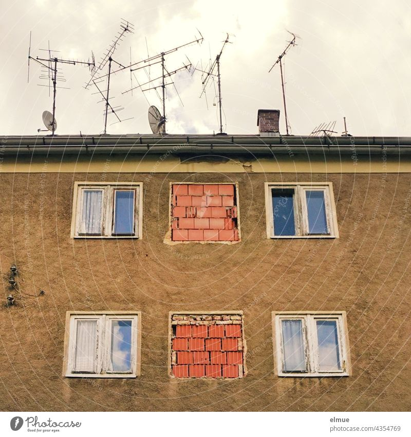 View of an old, unoccupied apartment building with windows, partly bricked up, and numerous old TV antennas as well as satellite dishes on the roof / dilapidated / core renovation / real estate