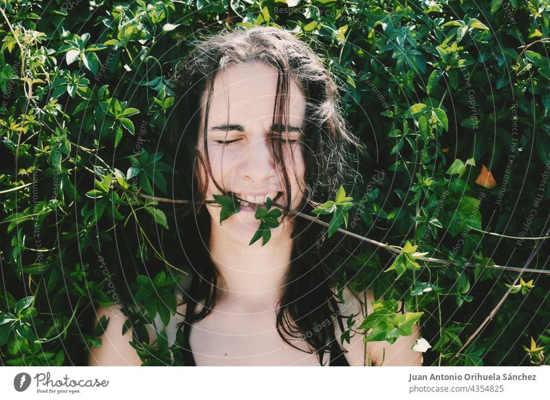 Strange image in which a young girl surrounded by plants bites the leaves. lovely brunette unusual eyes long haired funny outdoor caucasian park female bizarre