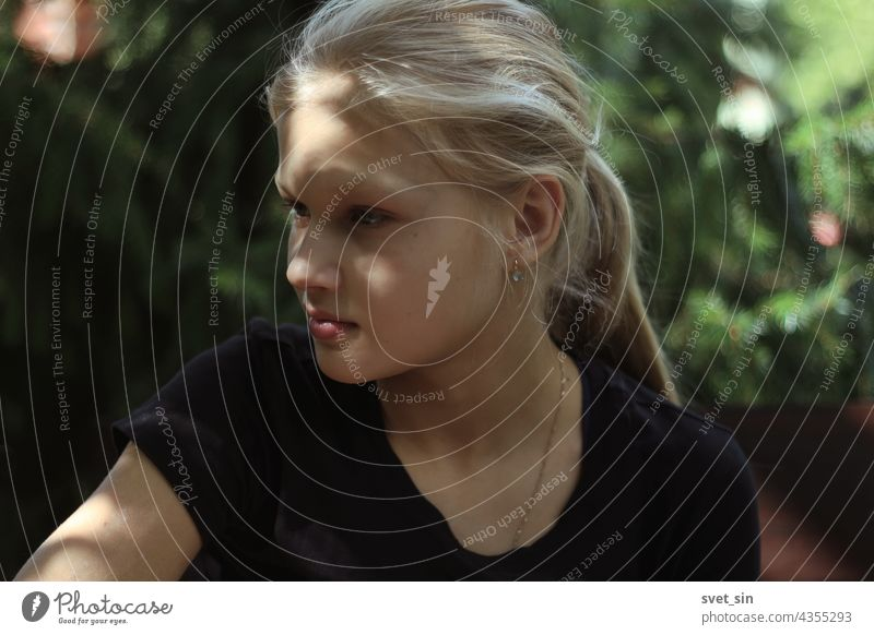 A blond teenage girl in a black T-shirt is sitting outdoors in the greenery and looking thoughtfully aside. Portrait of a pretty blonde girl in a semi-profile with sun glare on her face.