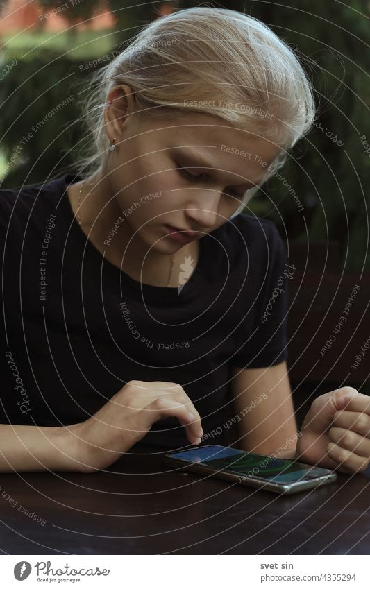 A blond teenage girl in a black T-shirt is sitting outdoors at a wooden table and flips through (reads) posts in social networks on her smartphone. blonde