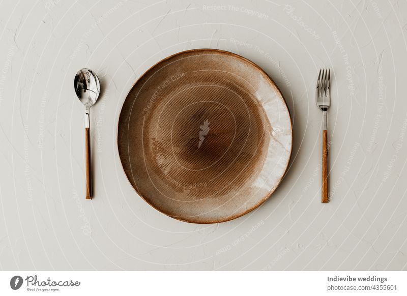 A brown plate with a spoon and a fork on beige background. Flat lay, top view. Brown and natural color plates. Textured grainy pattern on the plates. art bowl