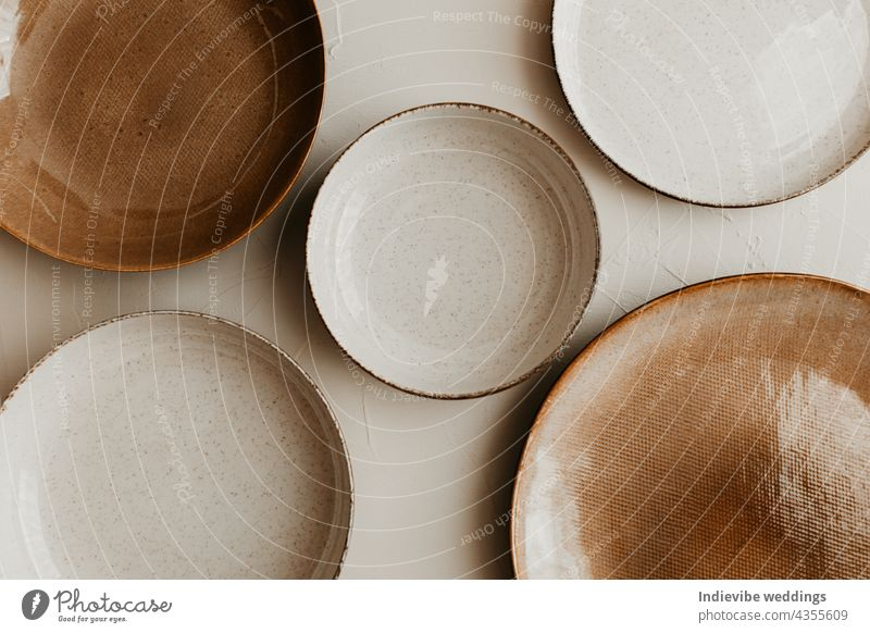 Five different size plate on beige background. Textured grainy pattern on the plates. Flat lay, top view. Brown and natural color plates. art bowl bowls