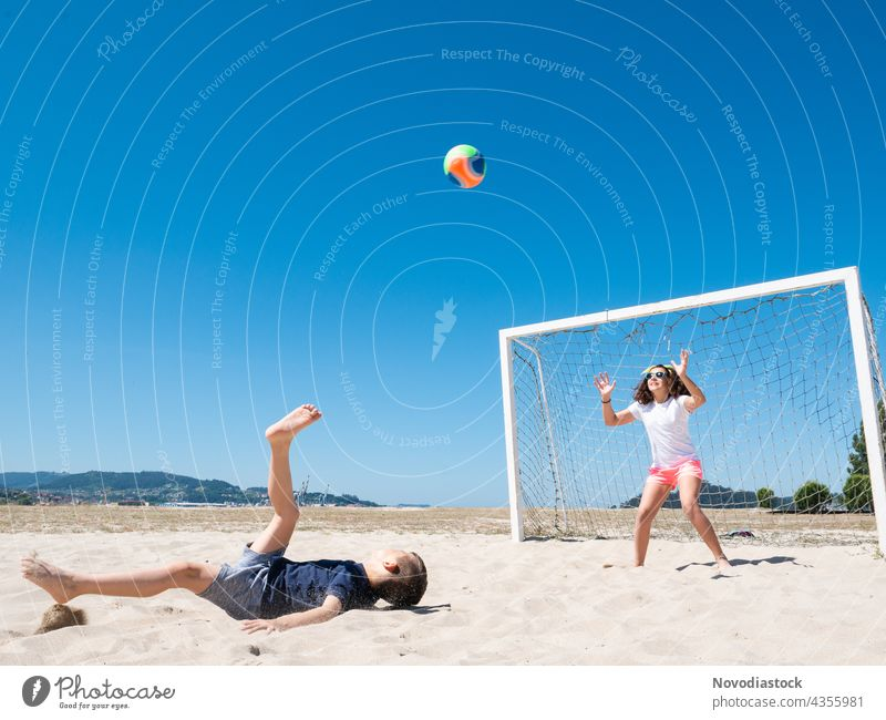 two children playing soccer on beach football happy water cheerful friendliness shore ocean summer casual sea together joy closeness smiling vacation sport