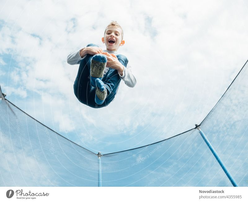 young boy jumping on trampoline male child alone 1 high outdoors smile enjoy happy action motion movement model casual healthy lifestyle jeans caucasian funny