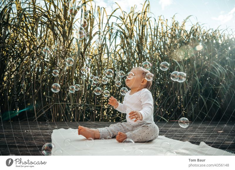 Baby sits on the floor in front of reeds and plays with soap bubbles Soap bubble Playing Joy Infancy Happy Child Happiness Blow Sky Common Reed Exterior shot