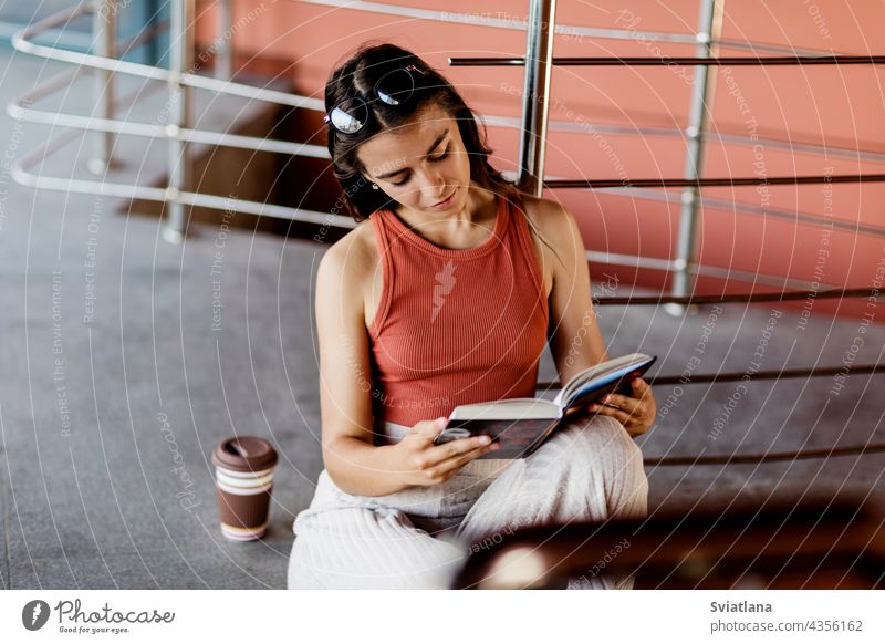 A student sits on the stairs on campus and reads a book, next to her is a glass of coffee girl sitting reading learning college school beautiful lifestyle day