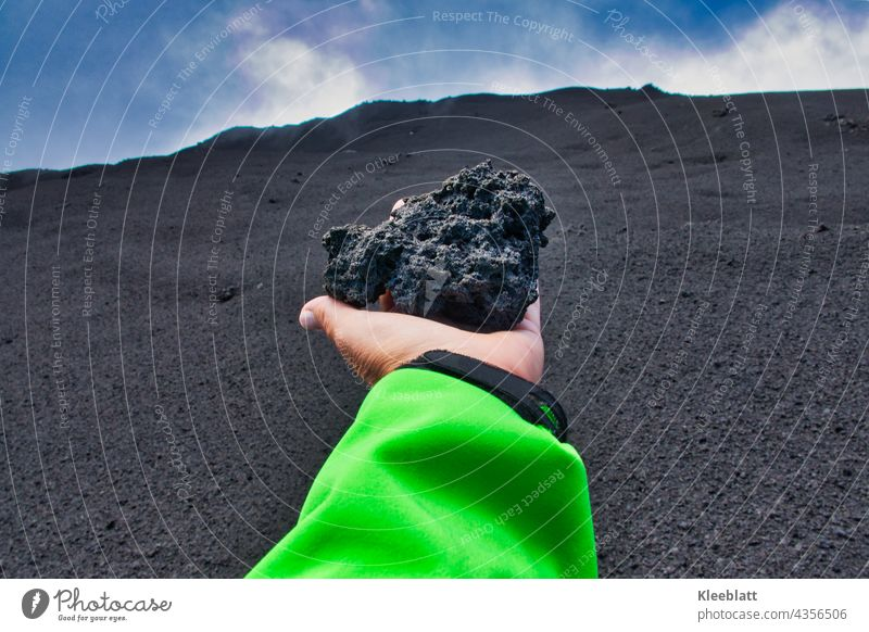 Etna - woman's hand holding a large volcanic ash lump in her outstretched hand towards the volcanic crater Women`s hand green jacket blue sky white clouds