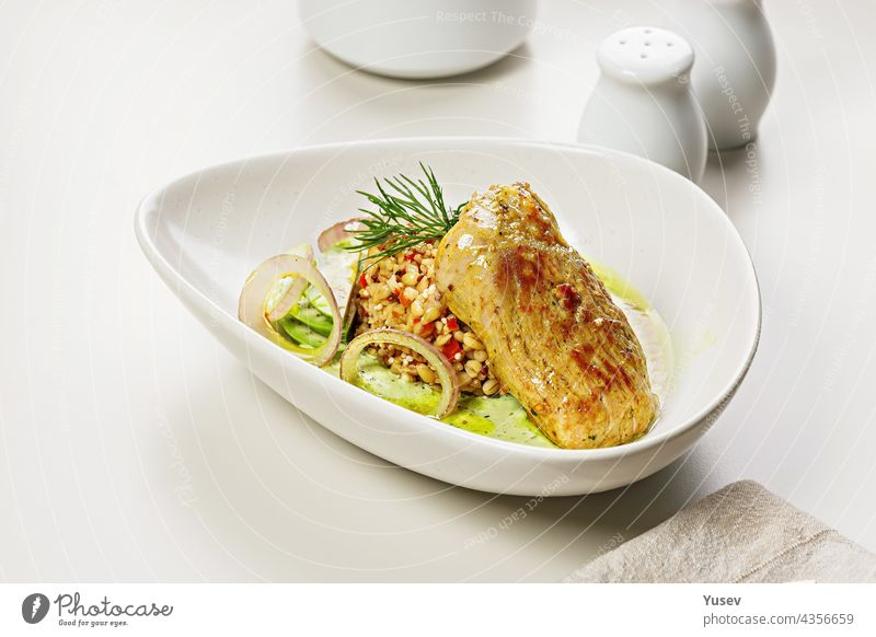 Turkey fillet with garnish and sauce. Baked turkey with bulgur, quinoa and vegetables. Restaurant dish. Cooked poultry with garnish. Food styling and food photography. Copy space. Light background