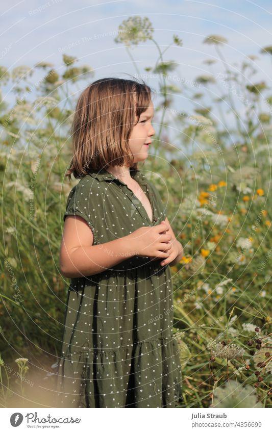 Girl in green polka dot dress stands in summer flower meadow flowers Flower meadow Dress dot pattern Chic Collar Summer Summery Infancy Child Kindergarten