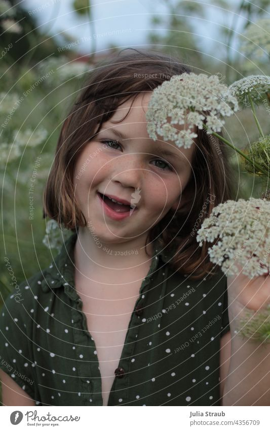 Girl standing in the middle of the flower meadow Umbellifer Wild carrot blossom Dyer's camomile Hemlock Observe look brown hair short hair Stand summer tan