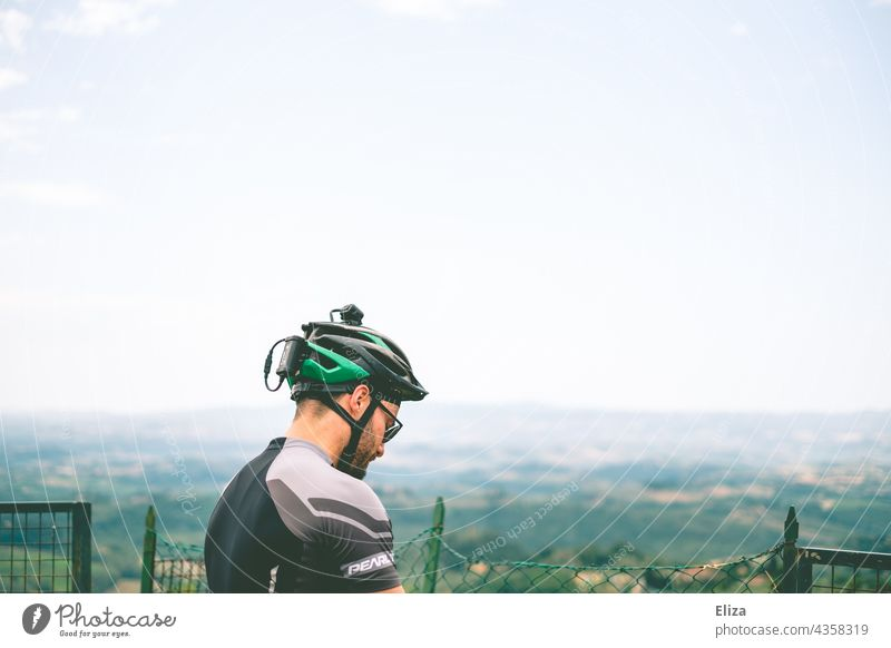 Man in cycling clothes with bicycle helmet in front of a view of the countryside Bike helmet Bicycle clothing Sportswear Cycling tour Landscape Vantage point
