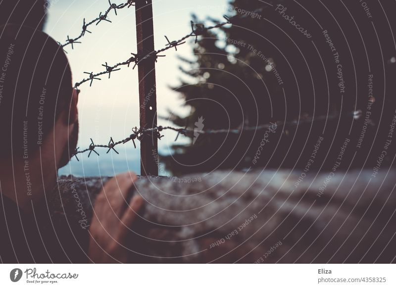Man looking over a fence with barbed wire. Concept of being trapped and wanderlust. Barbed wire Captured Fence jail Barbed wire fence Border Barrier Safety