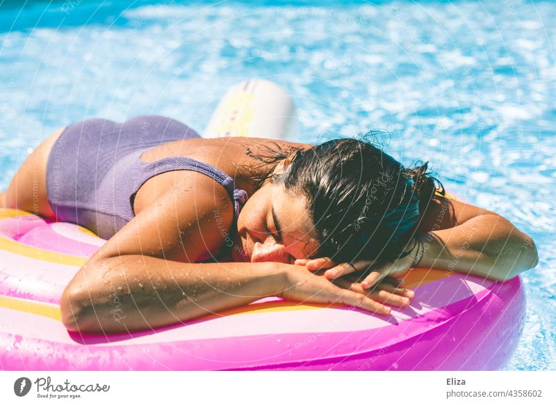 Woman with purple swimsuit lies in the pool on an air mattress and enjoys the sun Air mattress Swimsuit Summer Lie sunbathe Sun Relaxation vacation Water
