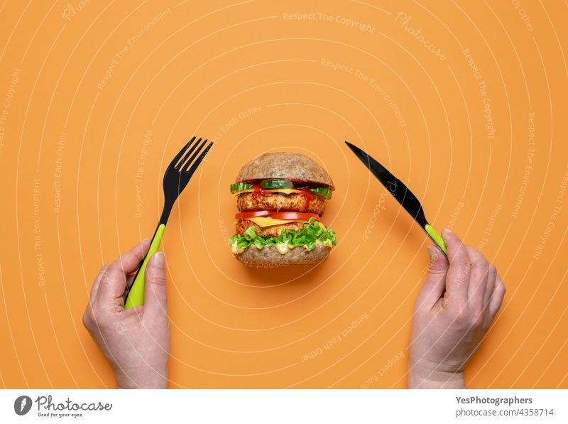 Eating vegan burger top view on an orange background. above alternative bread bun cheese cheeseburger color consumerism cuisine cut out delicious dinner double