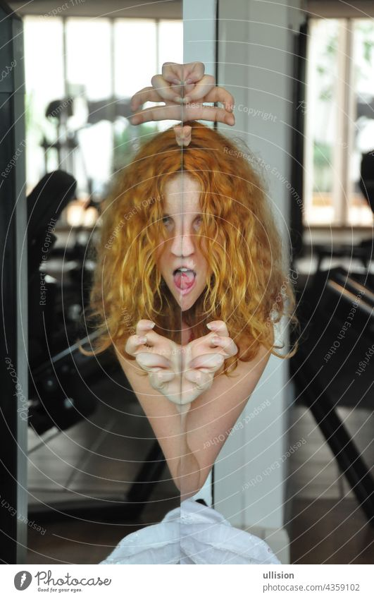 Portrait and hands of scary redhead woman with tongue out, creepy face in mirror, female duality, mental disorder, subconscious crisis portrait concept posing