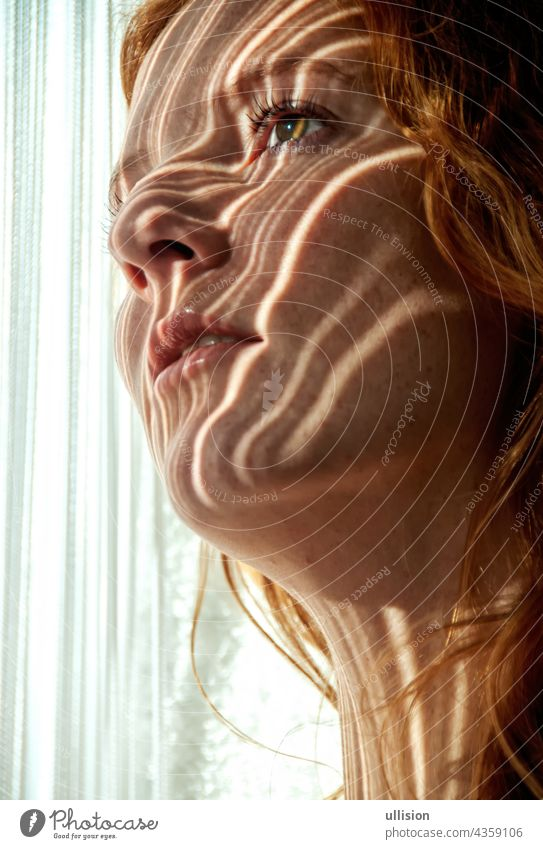Portrait of a beautiful young attractive sexy redhead woman, smiling seductively, shadow striped by the threads of a string curtain in the early morning sun