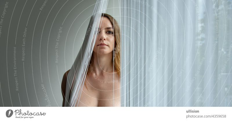 colored portrait of a young attractive woman behind a string curtain with copy space, place for text. thread blind sexy beautiful fall mask mouth chin nude