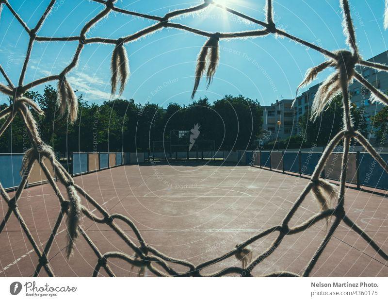 Framed view trough a net of a soccer field in a neighborhood entertainment league sport activity succeed goal football success lawn play shoot colours