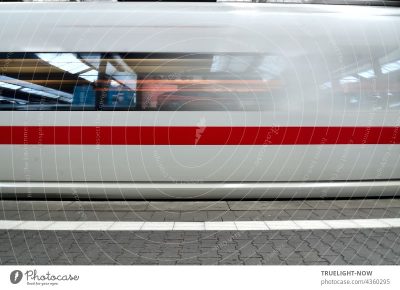 A snow-white ICE train with a thick red stripe is just leaving Munich Central Station. In its windows the station concourse is reflected with neon lights, the grey pavement of the platform shows a white stripe-n-.