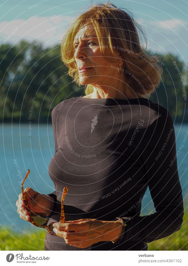 fit senior lady dressed in black by the lake woman portrait happy mature people female caucasian elderly old lifestyle retired beautiful smile person background