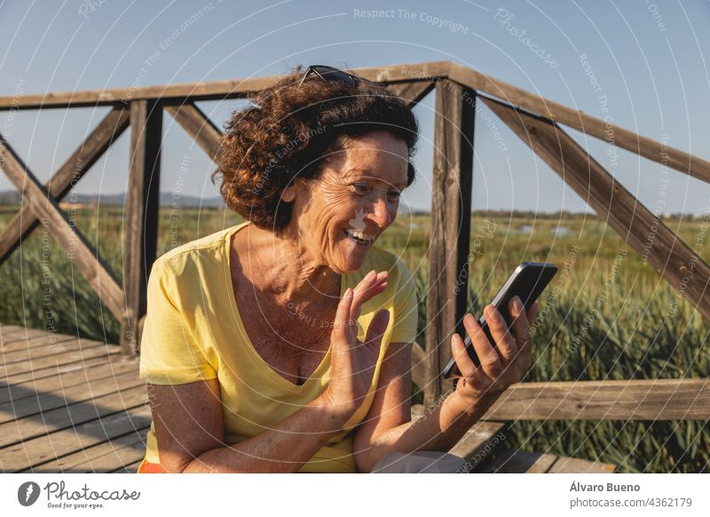 A cheerful and vital woman, in her 70s, greets while chatting with someone on a video call from a natural area of the Mediterranean, Spain waving saying hello