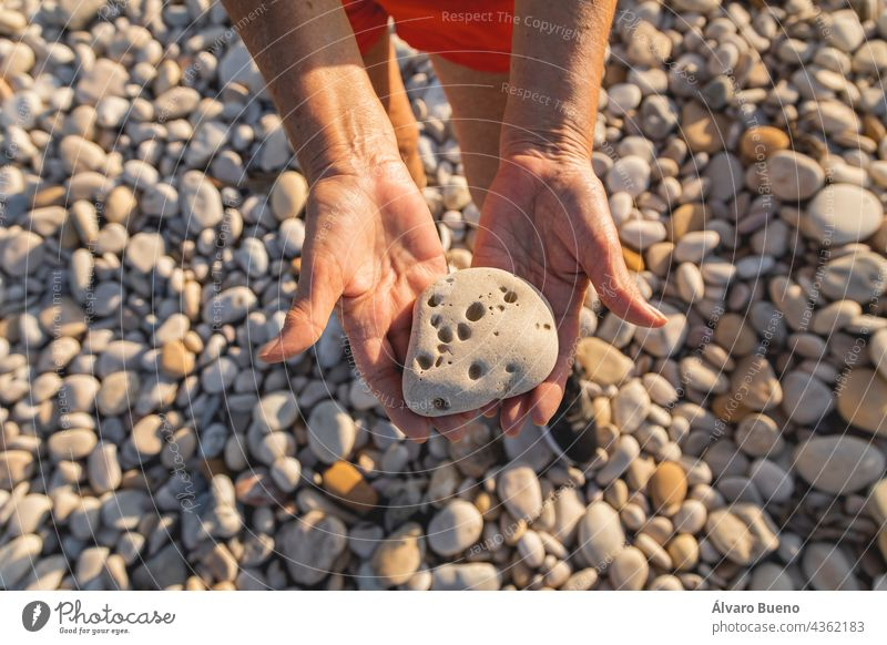 A woman, in her 70s, holds a stone full of holes, on a natural beach, next to the Mediterranean Sea, Spain texture object pebble beach hands close-up senior