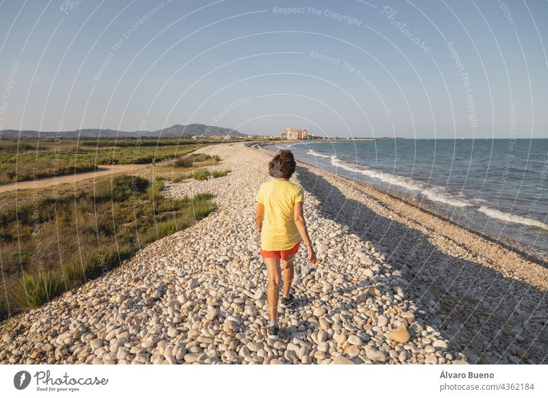 A cheerful and vital woman, in her 70s, walks along a natural pebble beach at sunset, by the Mediterranean Sea, Spain take a walk walking on the beach