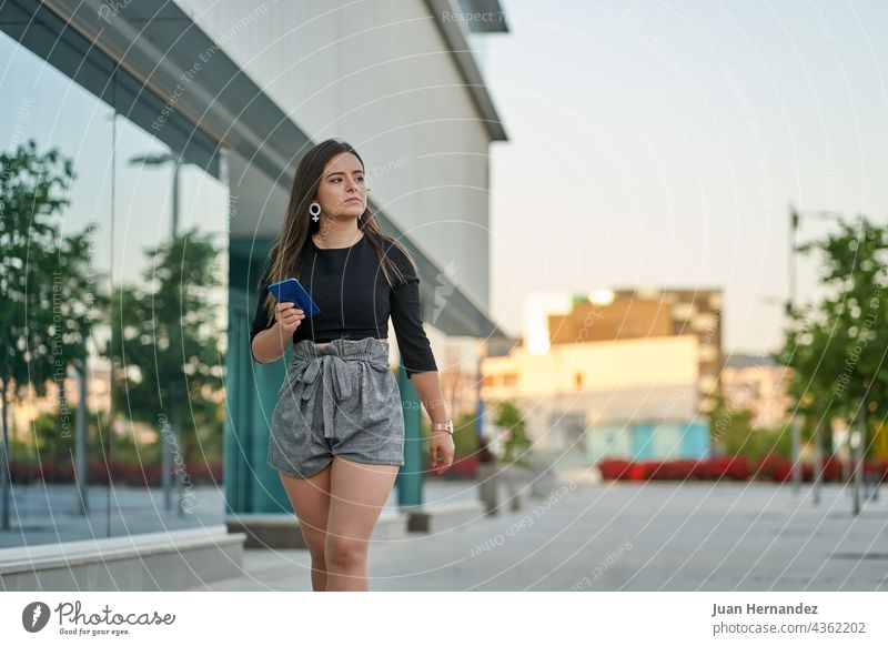 young woman walks with mobile phone in hand next to an office telephone smart phone smartphone cellular cellphone cell phone walking go lady women clock