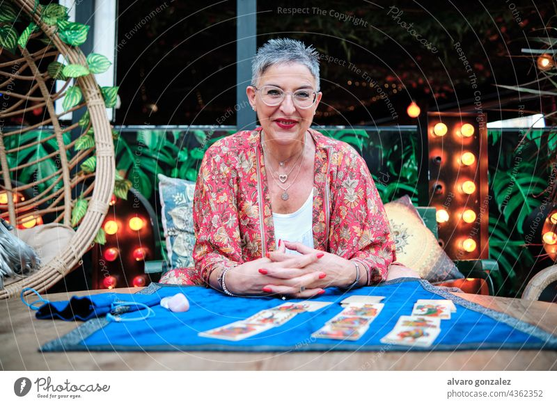 mature woman with grey hair using tarot cards to predict future caucasian adult confident elder witch female fortune portrait prophet mystery mystic reading