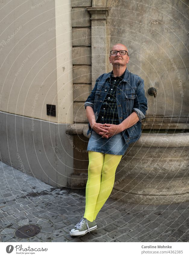 Man in jeans mini and yellow pantyhose sits on a fountain and looks satisfied Fashion Fashion Model Lifestyle Style Face Skirt support Human being Happy Well