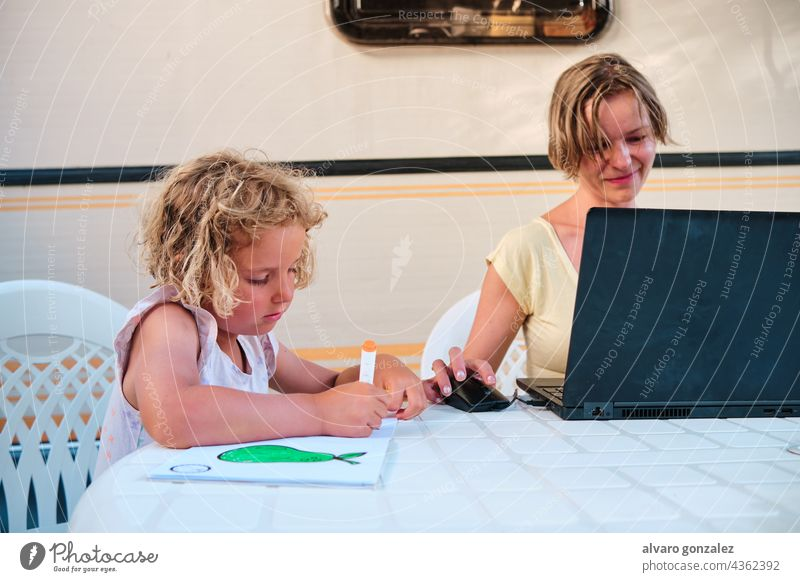 daughter drawing while mother works while in holidays in a camping caravan summer business woman family people laptop young boy internet office busy campsite