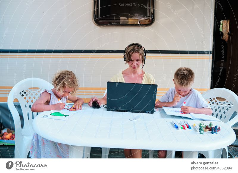 a family in a caravan at a camping. Mother working and children having a leisure time drawing holiday summer business woman people laptop young boy internet