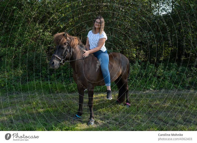 Young woman sitting contentedly on an Icelandic horse Woman Human being Adults Exterior shot Horse Icelander Bangs Brunette 18 - 30 years Colour photo