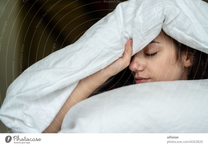 Portrait of an attractive, young, sexy dark haired woman in Bed, hand and head on the pillow under the blanket, Copy space. Sleep sleeping people bed white